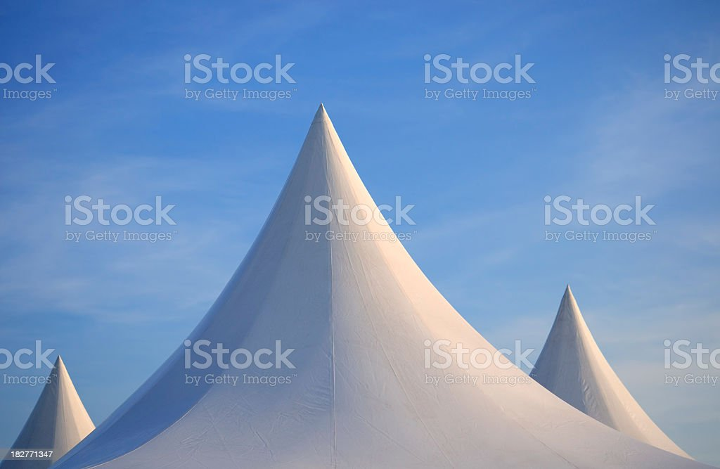 Three white spiked tent tops against deep blue sky royalty-free stock photo