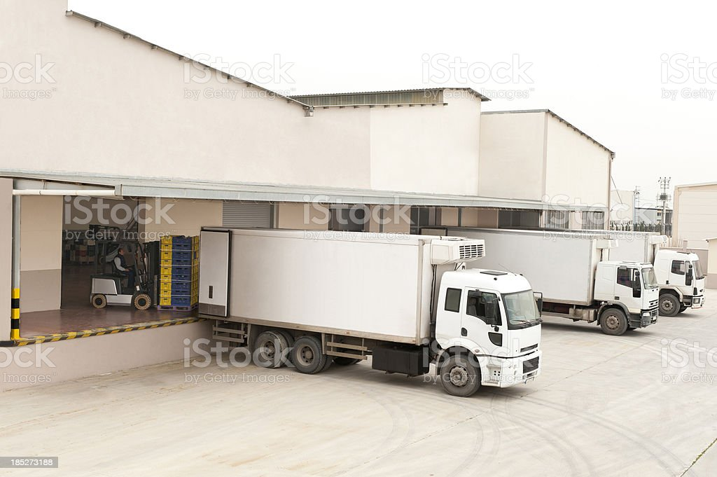 Three white trucks in front of a warehouse stock photo