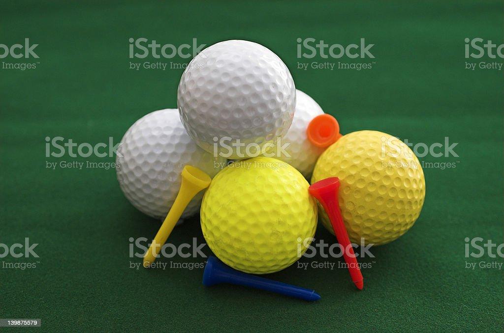 Three White Two Yellow Golf Balls royalty-free stock photo