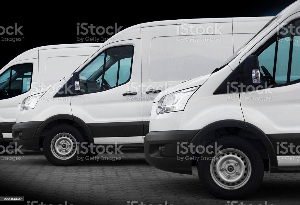 Three white vans on black stock photo