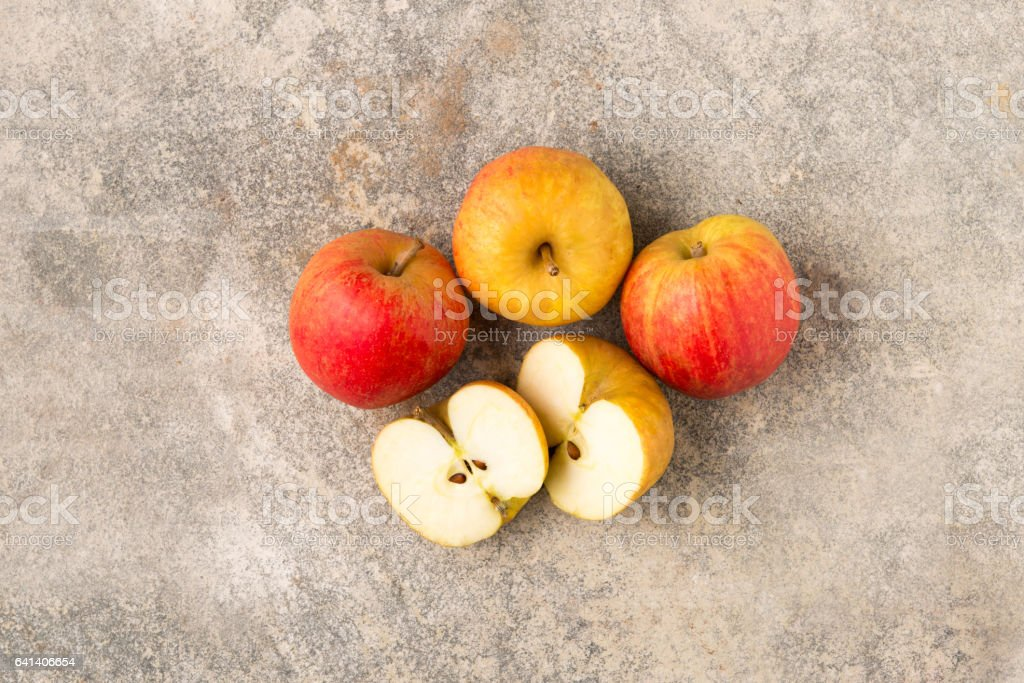 Three Whole and a Sliced Apple stock photo