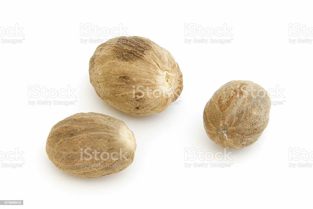 Three whole nutmegs on white royalty-free stock photo