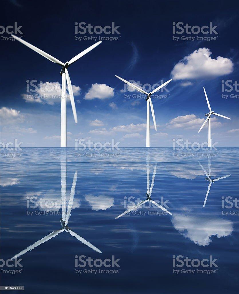 Three Wind Turbines Reflected on the Ocean stock photo
