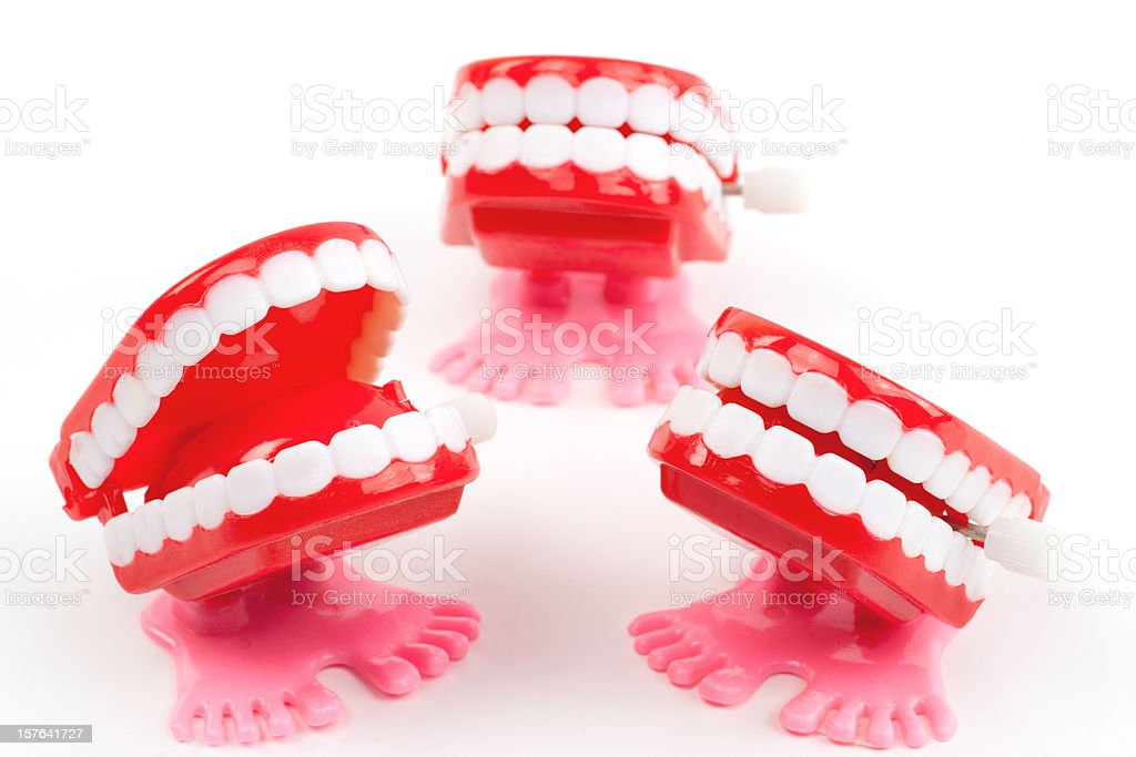 Three wind up chattering teeth toys on white stock photo