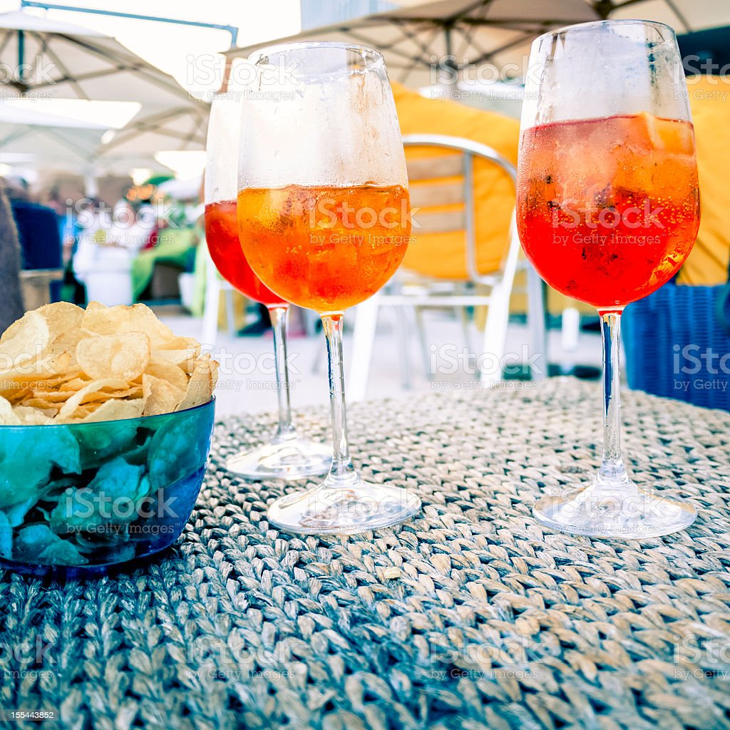 Three wine glasses with orange drinks on a table with chips stock photo
