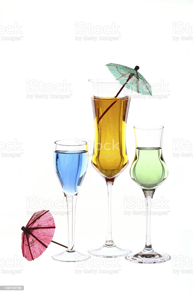 Three wineglasses are filled with colored beverages and cocktail umbrellas stock photo