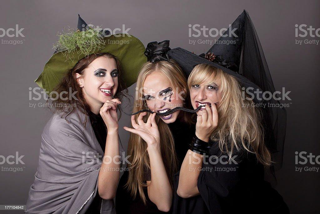 three witches eat  black snake stock photo