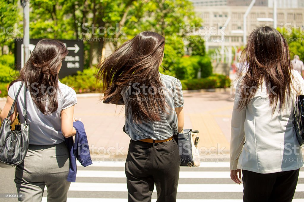 Three woman with long hair crossing the street stock photo