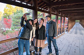Three women and a guy taking pictures on wooden bridge