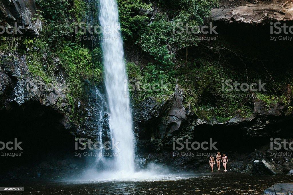 Three Women by a Waterfall in Hawaii stock photo