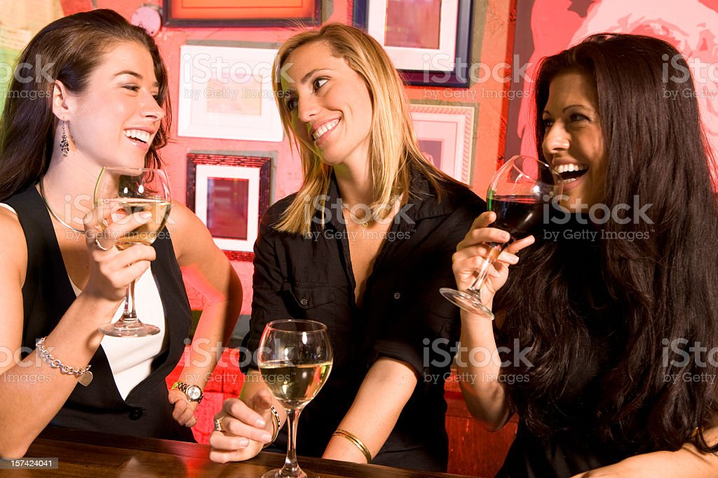 Three women chatting and drinking wine in a bar royalty-free stock photo