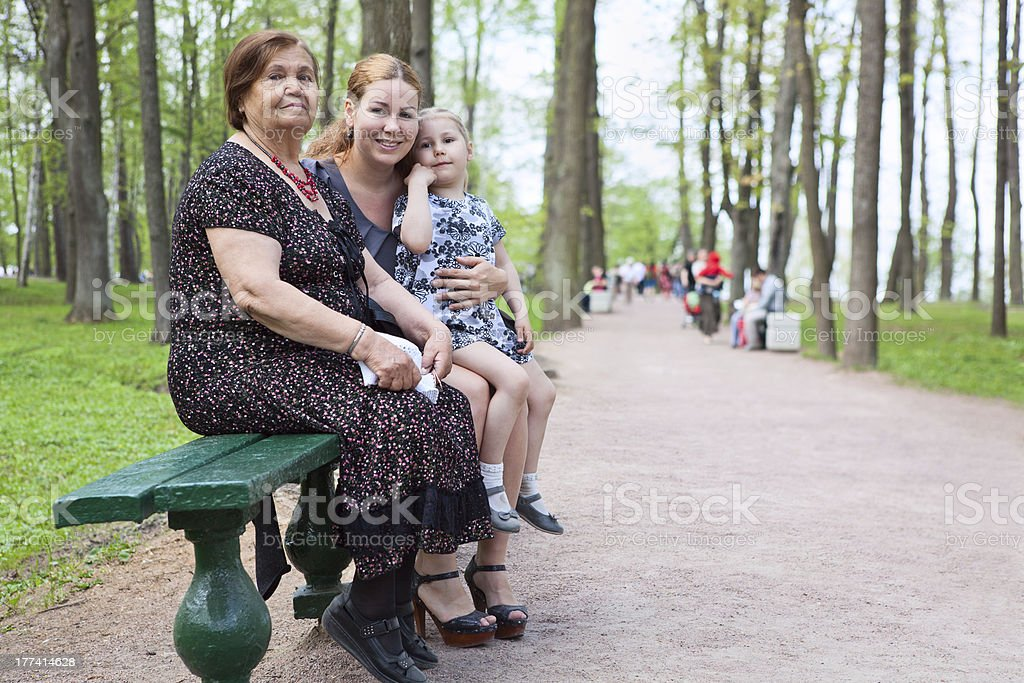 Three women different ages are sitting on bench in park royalty-free stock photo