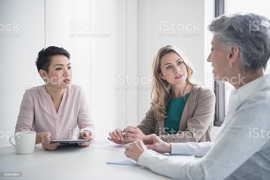 Three women discussing in business meeting stock photo