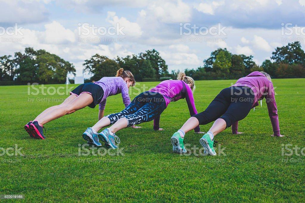 Three women doing push ups in park stock photo