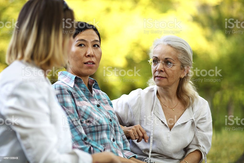 Three women having a serious discussion at a park royalty-free stock photo