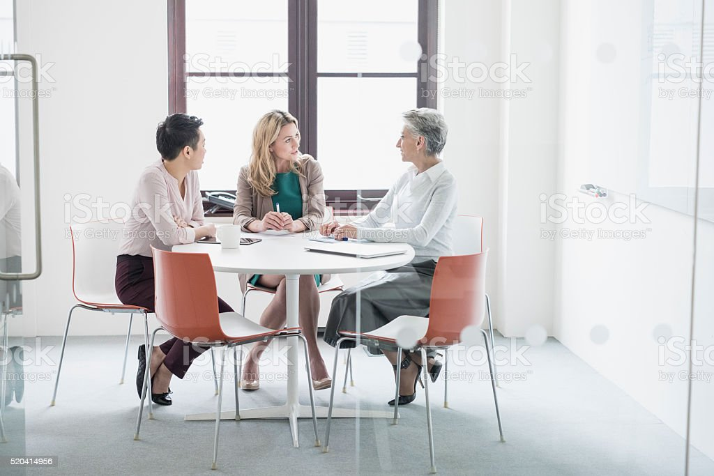 Three women having business meeting in modern office stock photo