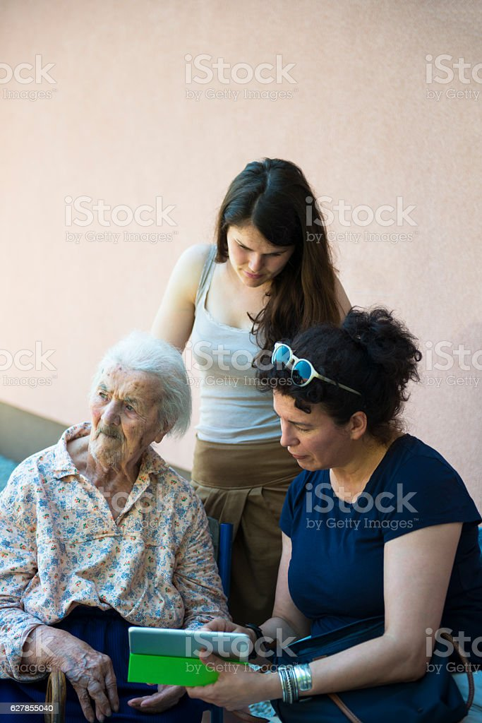 Three women in discussion over photo memories on tablet stock photo