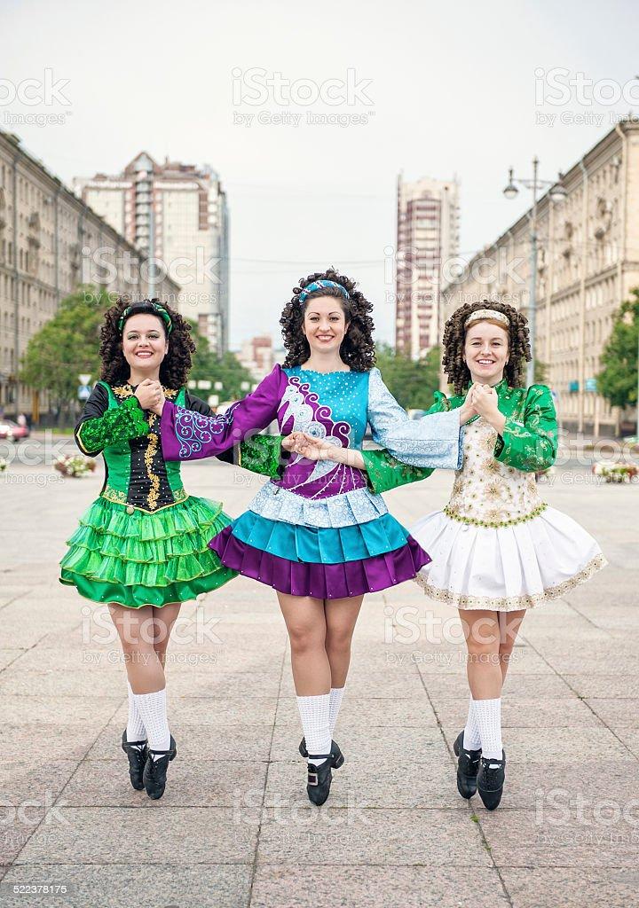 Three women in irish dance dresses and wig posing stock photo