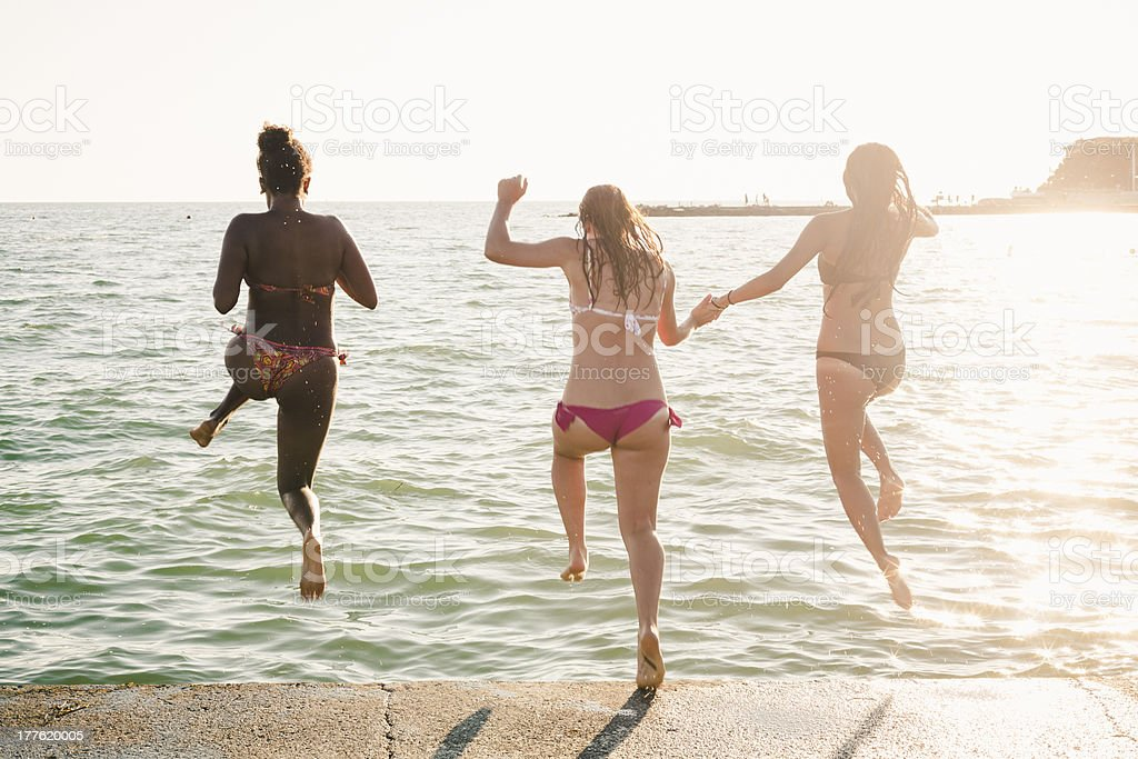 Three women jumping into the sea during summer royalty-free stock photo