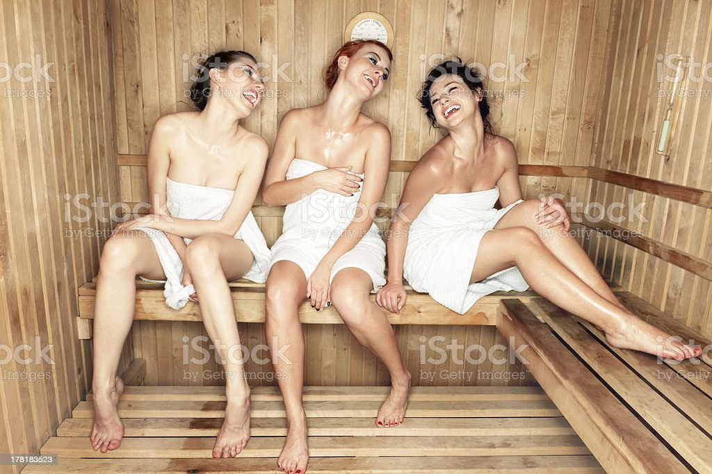 Three women laughing in a sauna stock photo