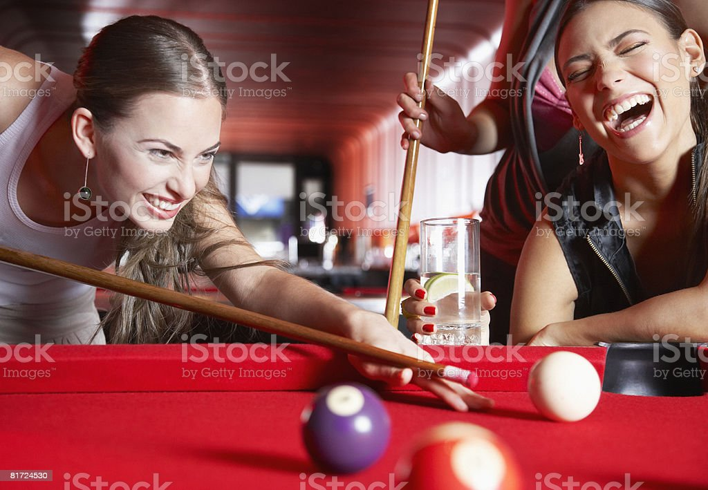 Three women playing pool and laughing royalty-free stock photo