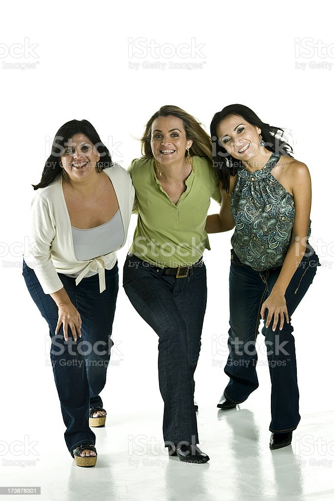 three women posing for the camera against a white backdrop stock photo