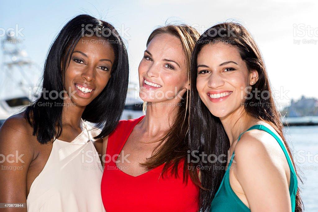 Three women posing in marina harbor. stock photo