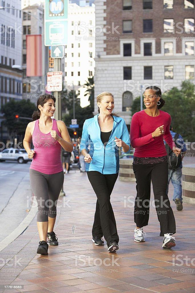 Three women power walking on urban street stock photo