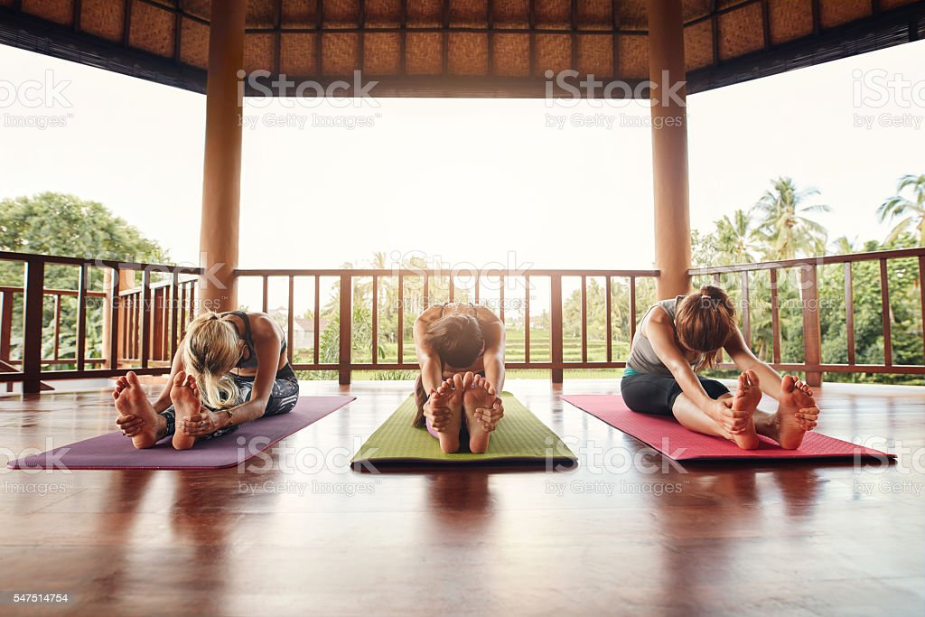Three women practicing paschimottanasana pose at yoga class stock photo