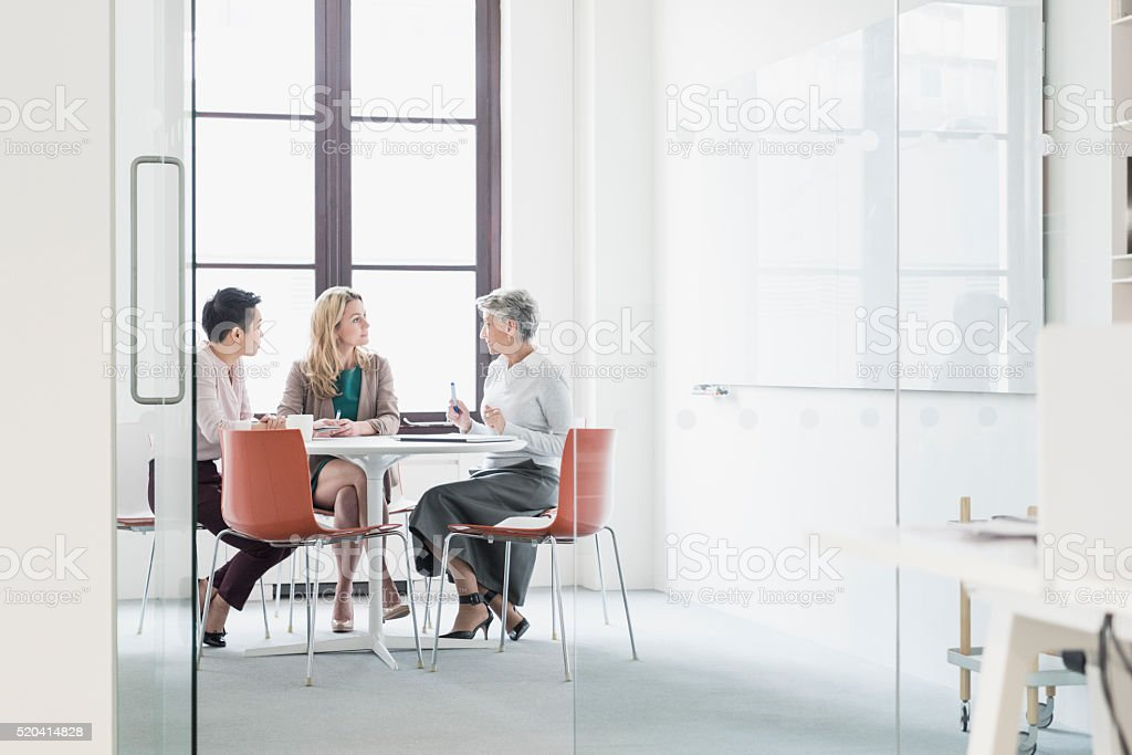 Three women sitting at table in modern office stock photo