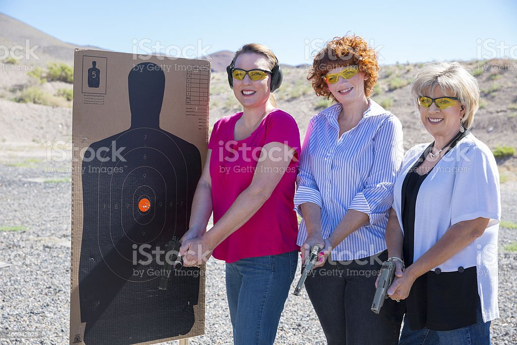 Three women standing by a target outdoors with their handguns royalty-free stock photo