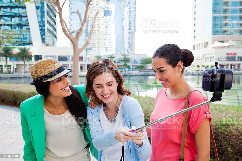 Three women take selfie in Dubai Jumeirah Lake Towers. stock photo
