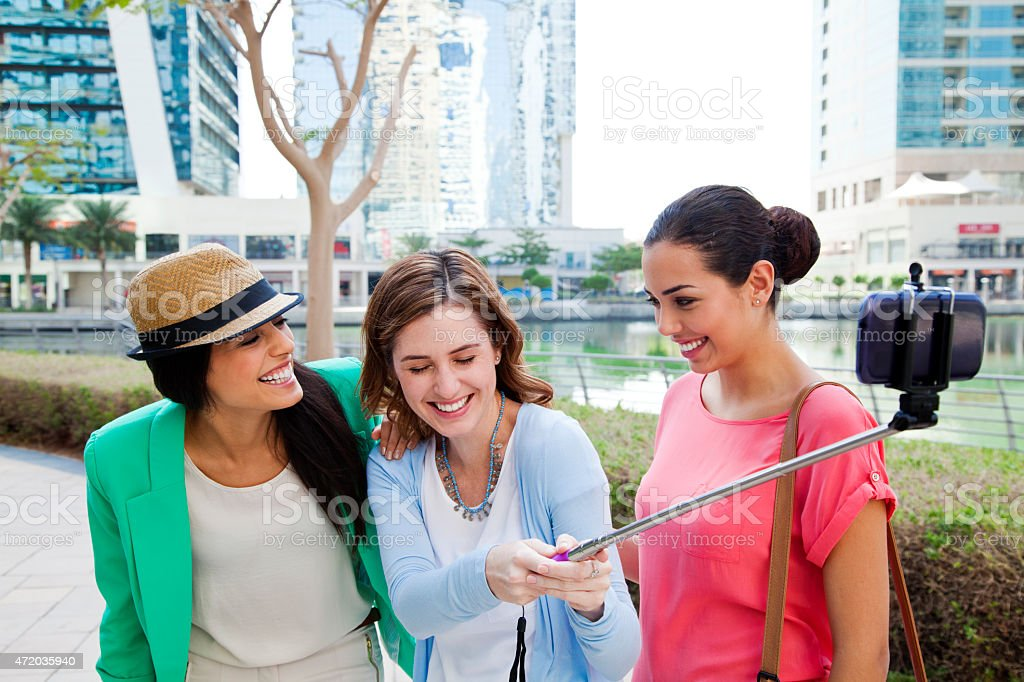 Three women take selfie in Dubai Jumeirah Lake Towers. stock photo