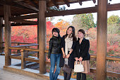 Three women taking pictures with autumn leaves on wooden bridge