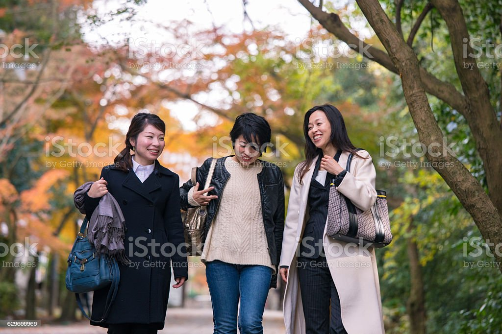 Three women walking together under autumn foliage with smile stock photo