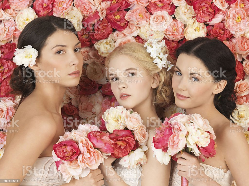 three women with flowers over roses background stock photo