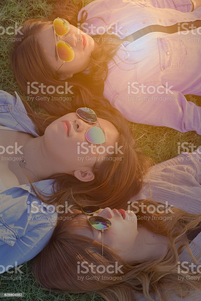 Three women with sunglasses on,lay down on green grass. stock photo