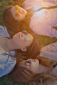 Three women with sunglasses on,lay down on green grass.