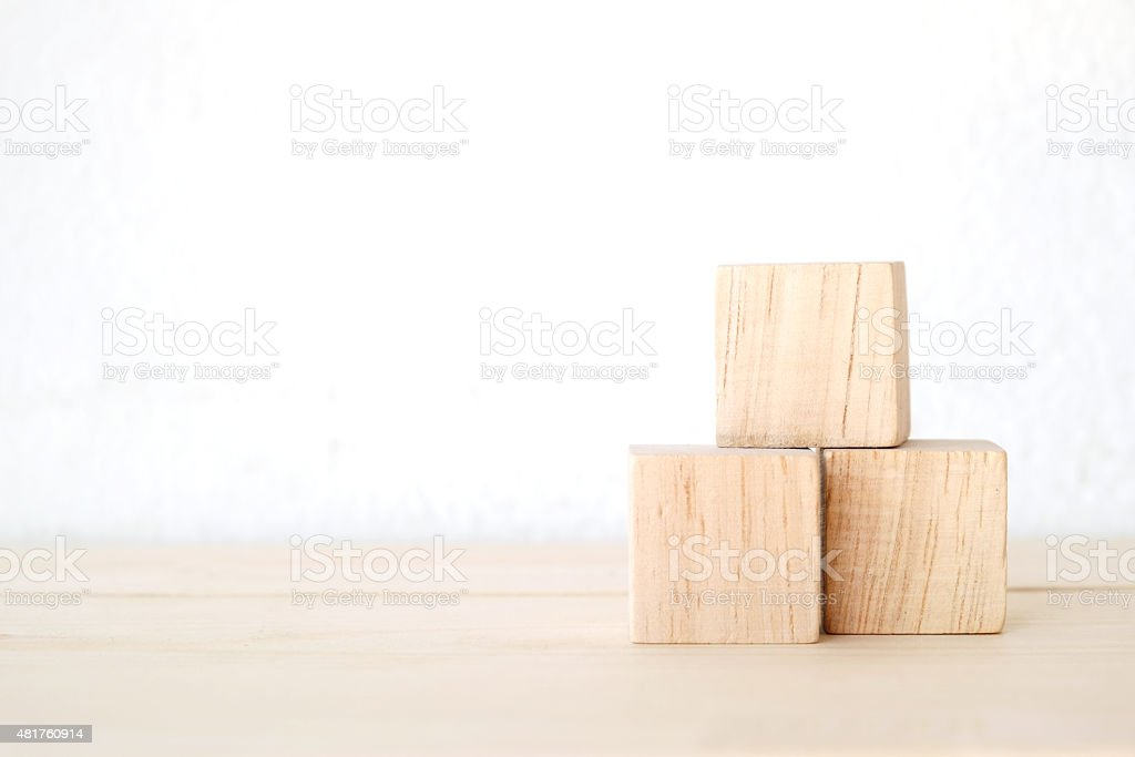 Three wooden cubes on table stock photo