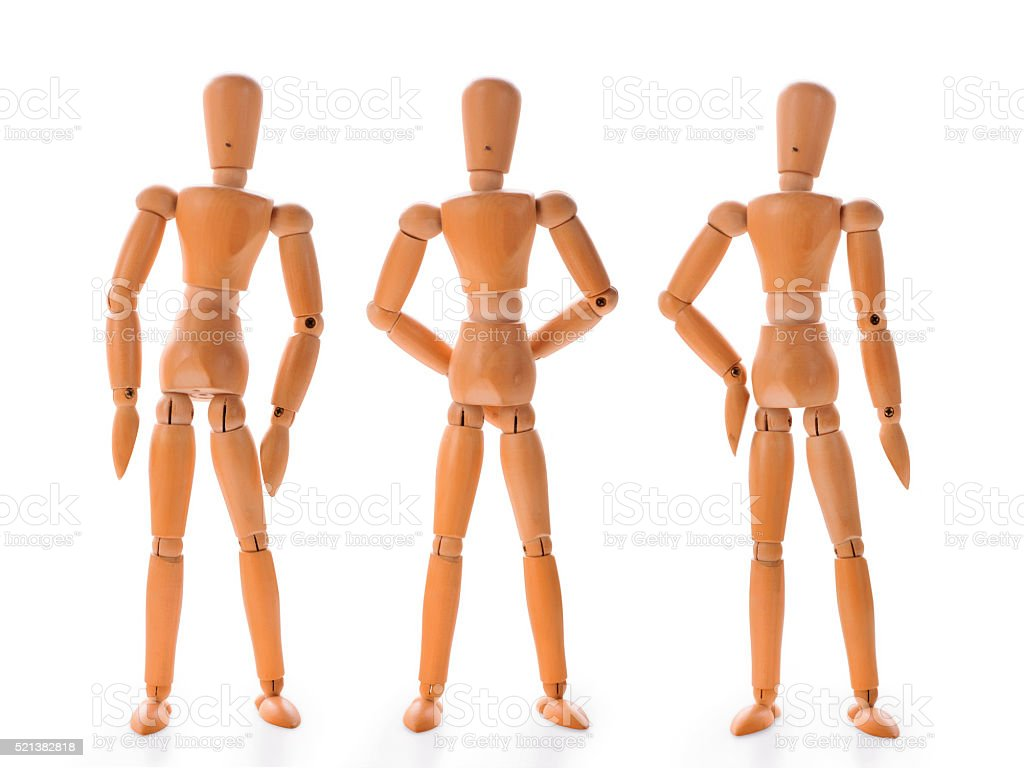 Three wooden dolls in different poses stock photo