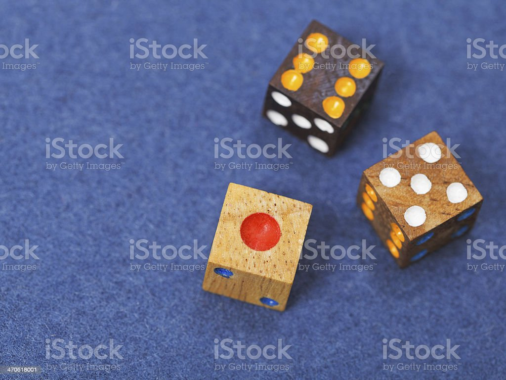 three wooden gambling dices on blue cloth stock photo