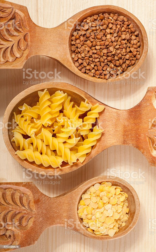three wooden spoon with buckwheat, lentil and pasta fusilini stock photo