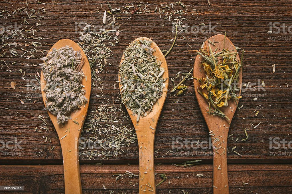 Three wooden spoons with different tea herbs stock photo