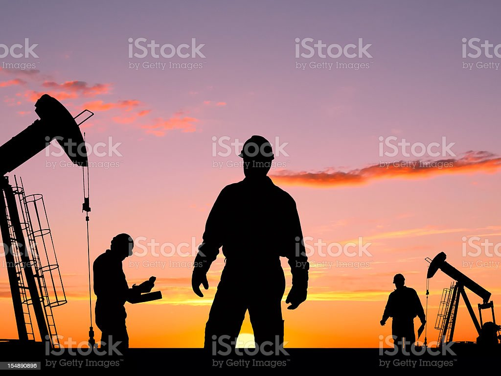 Three Workers and Two Oil Pumps At Dawn royalty-free stock photo