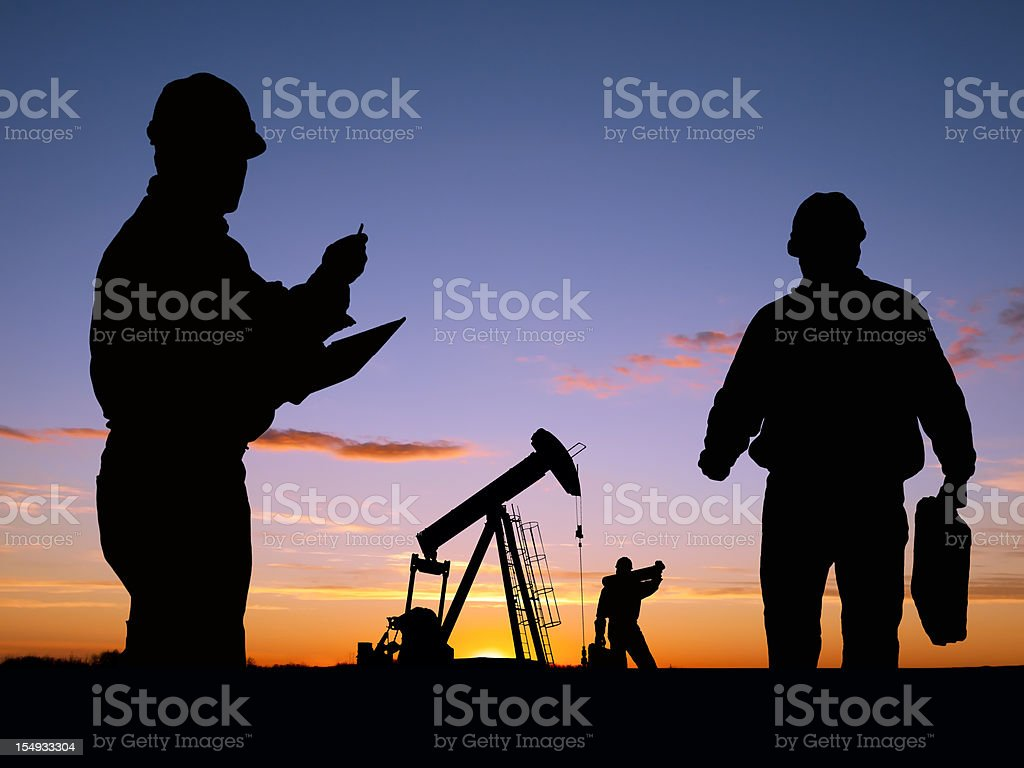 Three Workers Doing Business At Oil Well Pumpjack stock photo
