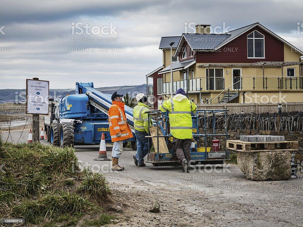 Three workmen alongside lifting platform royalty-free stock photo