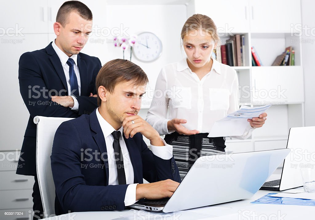 three worried coworkers in firm office stock photo