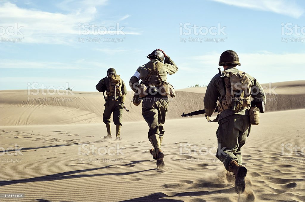 Three WWII Soldiers Running In The Desert Sand stock photo
