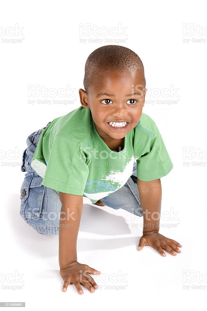 Three year old black boy on his haunches smiling stock photo
