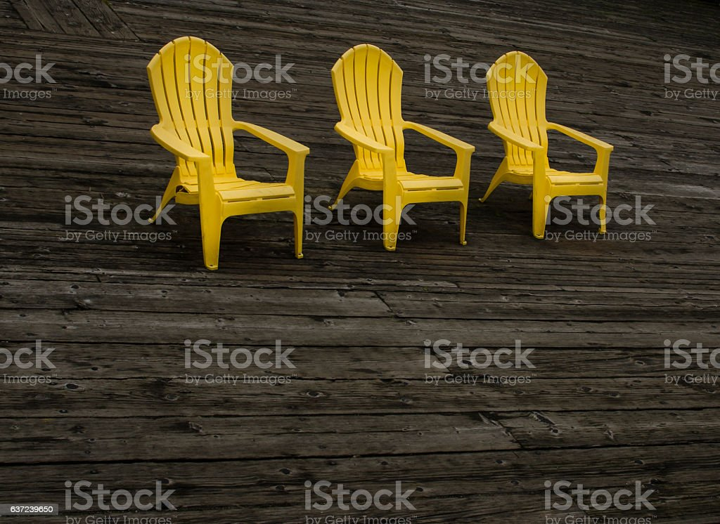 Three Yellow Chairs on Wooden Dock stock photo